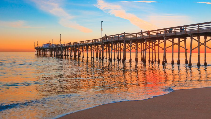Incoming tide reflects the sunsent at Balboa Pier in Newport Beach, CA